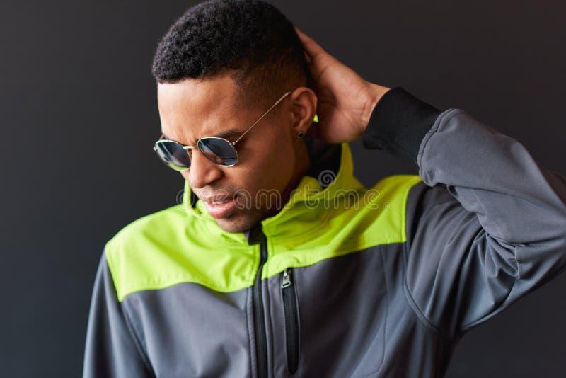 Homem afro-americano novo que veste os óculos de sol redondos do espelho que tocam em sua cabeça e que olham de sobrancelhas fran foto de stock