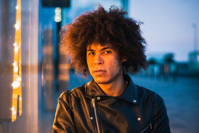 Homem afro-americano parecendo jovem sério iluminado pela luz da mostra na rua fotografia de stock royalty free