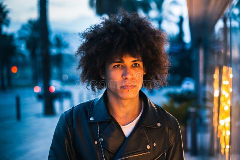 Homem afro-americano parecendo jovem sério iluminado pela luz da mostra na rua imagens de stock royalty free
