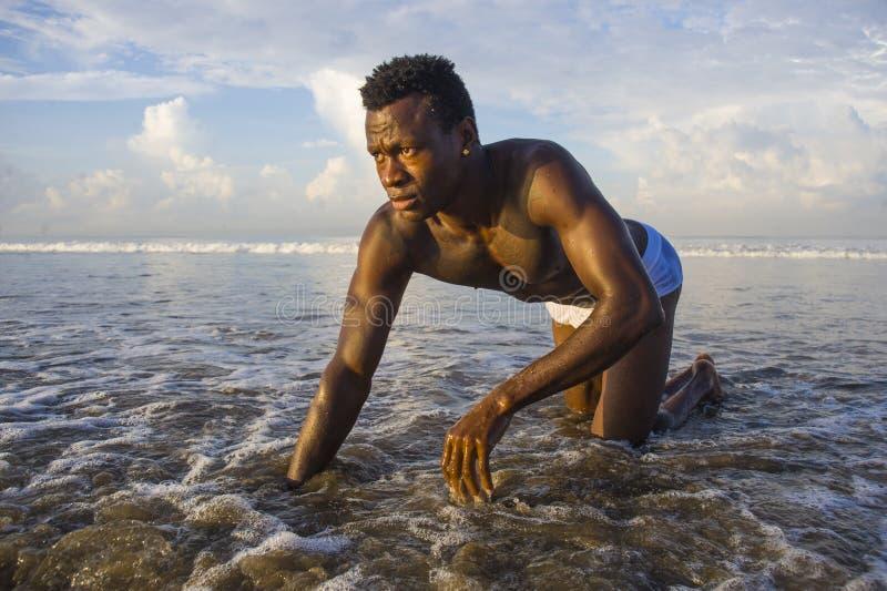 Homem afro-americano preto atrativo e 'sexy' novo com o levantamento atlético do corpo muscular fresco na água do mar na praia do imagens de stock royalty free