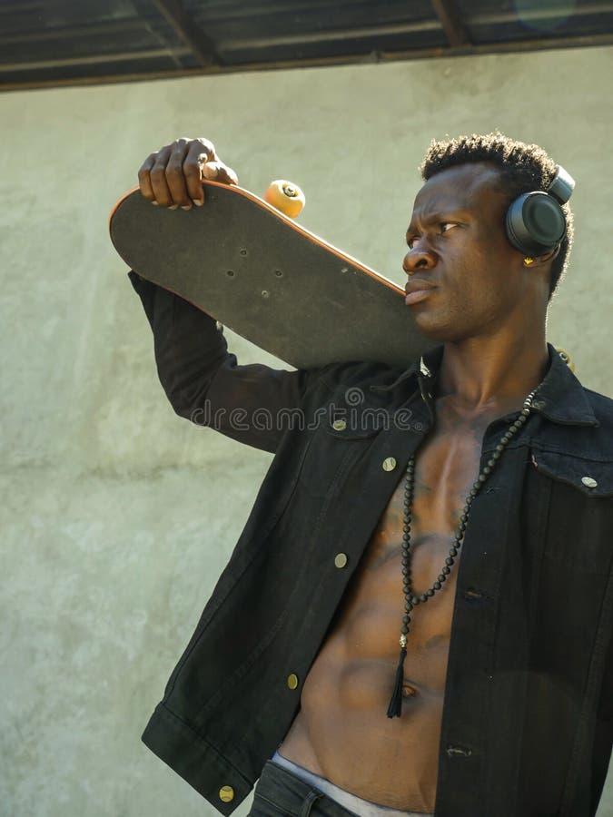 Homem afro-americano preto novo isolado fresco do moderno atrativo e seguro que anda na placa do patim da terra arrendada da rua  fotografia de stock royalty free