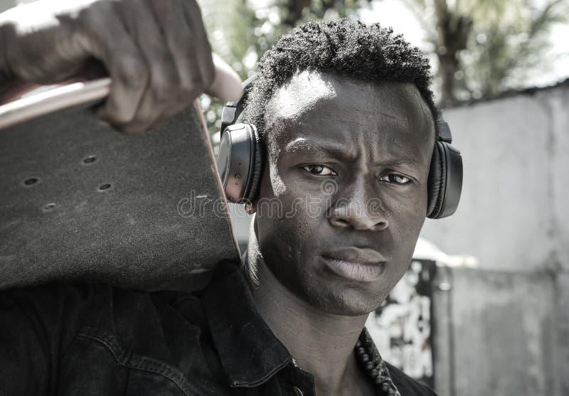 Homem afro-americano preto novo isolado fresco do moderno atrativo e seguro que anda na placa do patim da terra arrendada da rua  imagens de stock royalty free