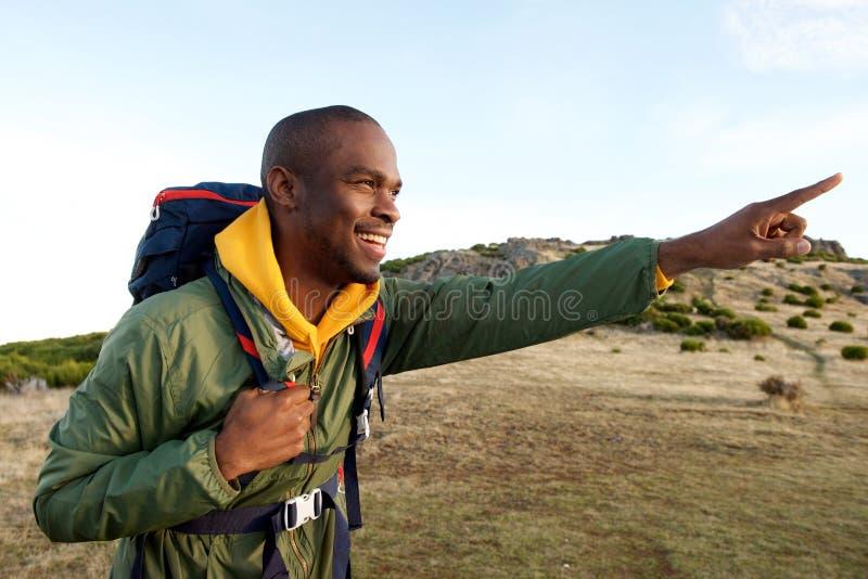 Homem afro-americano que caminha com trouxa e que aponta no sentido imagens de stock
