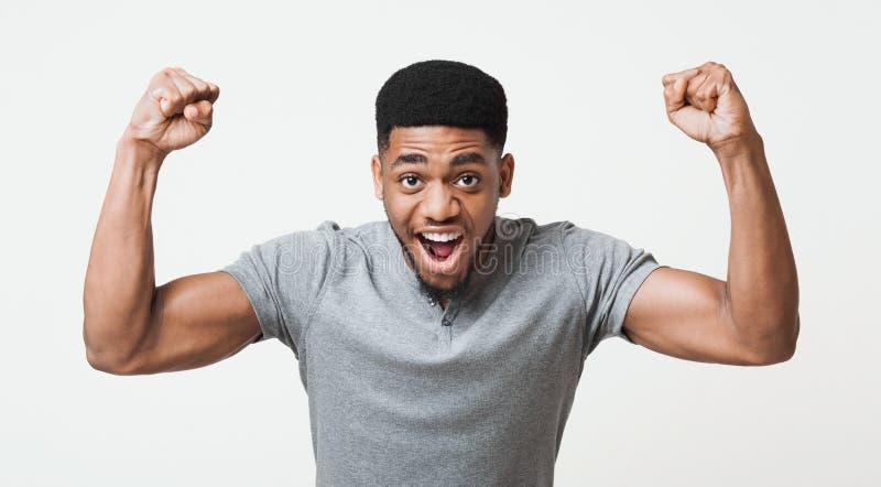 Homem afro-americano que grita e que mostra o bíceps na câmera foto de stock royalty free