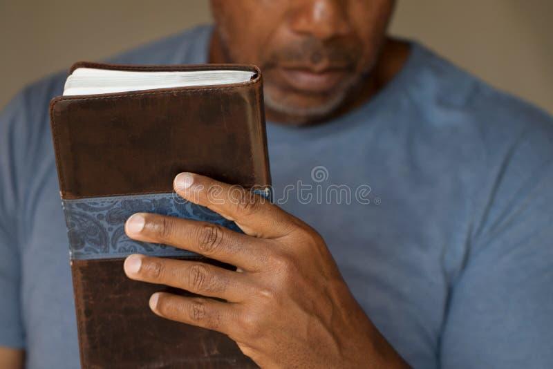 Homem afro-americano que guarda a Bíblia fotos de stock
