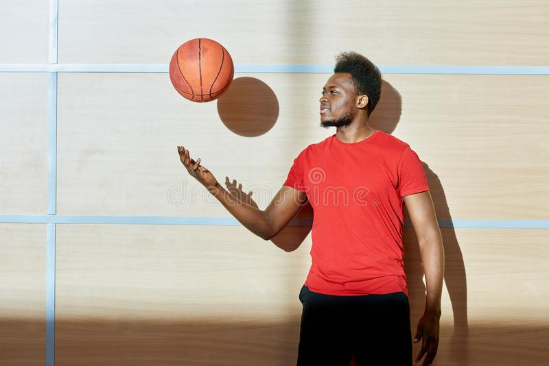 Homem afro-americano que joga acima a bola do basquetebol foto de stock royalty free