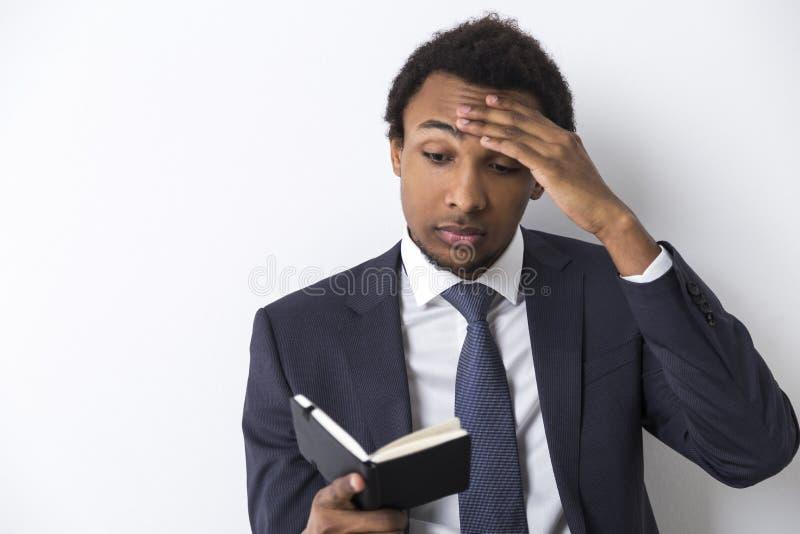 Homem afro-americano que lê um caderno preto foto de stock
