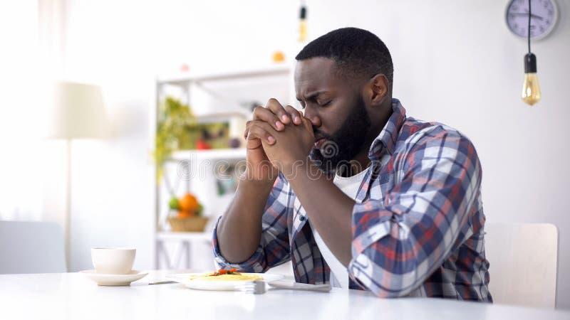 Homem afro-americano que reza antes do almoço, agradecendo ao deus para a refeição, religião foto de stock royalty free