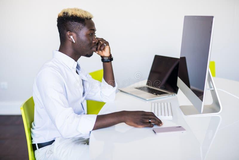Homem afro-americano que trabalha no centro de atendimento Gerente com computador homem no local de trabalho Consultante com micr fotografia de stock