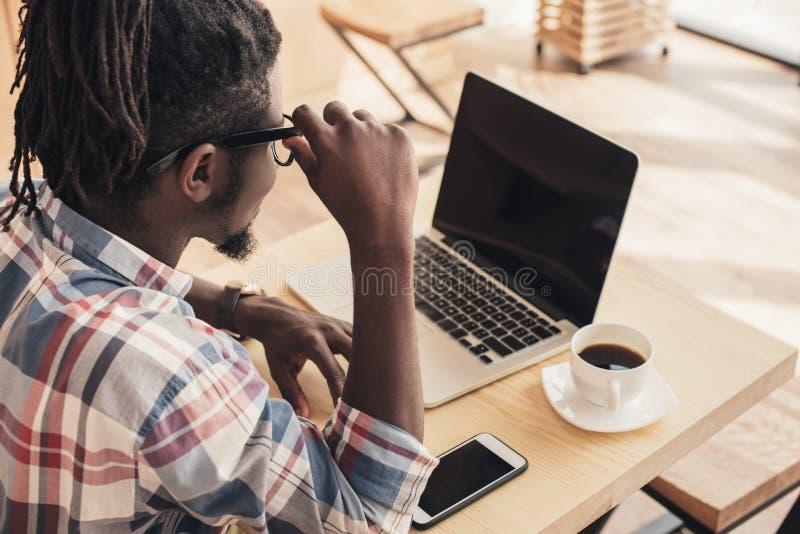 homem afro-americano que usa o portátil e o smartphone com telas vazias fotografia de stock royalty free