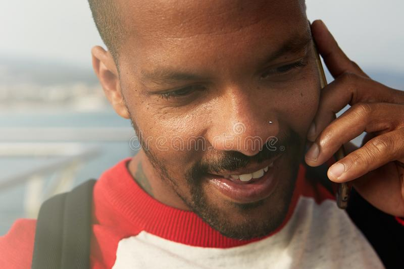 Homem afro-americano que usa o telefone celular na praia Homem urbano de sorriso feliz novo do moderno que veste a roupa informal fotos de stock