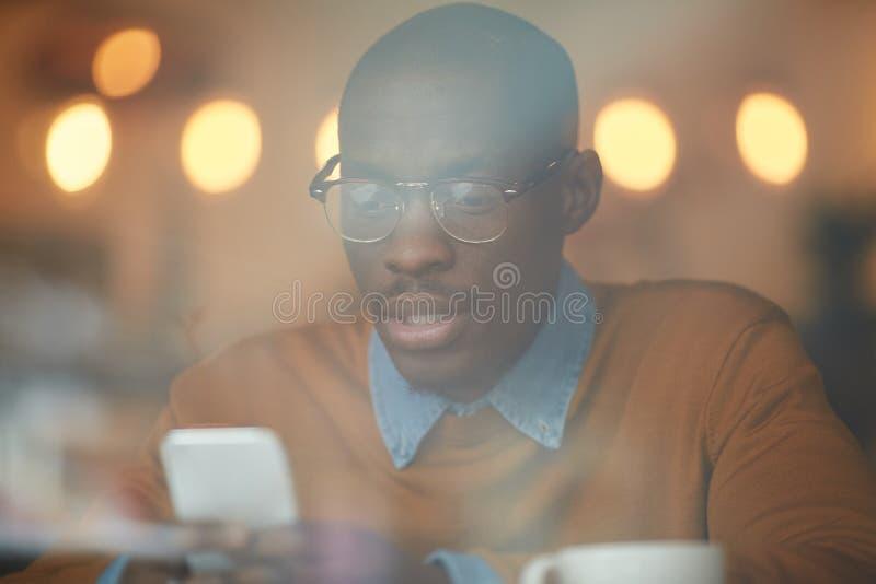 Homem afro-americano que usa Smartphone no bar foto de stock