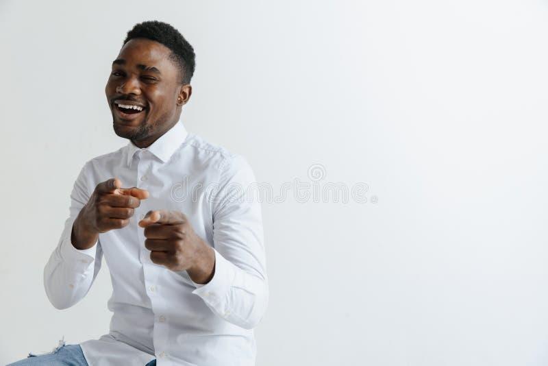 Homem afro-americano sobre o fundo cinzento isolado que aponta com o dedo à câmera e a você fotografia de stock royalty free