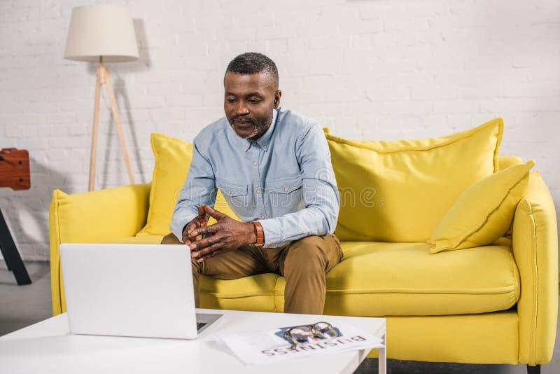 homem afro-americano superior que senta-se no sofá e na vista fotografia de stock royalty free
