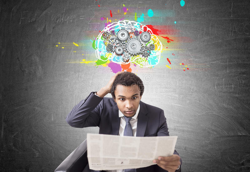 Homem afro-americano surpreendido, jornal, rodas denteadas do cérebro imagens de stock