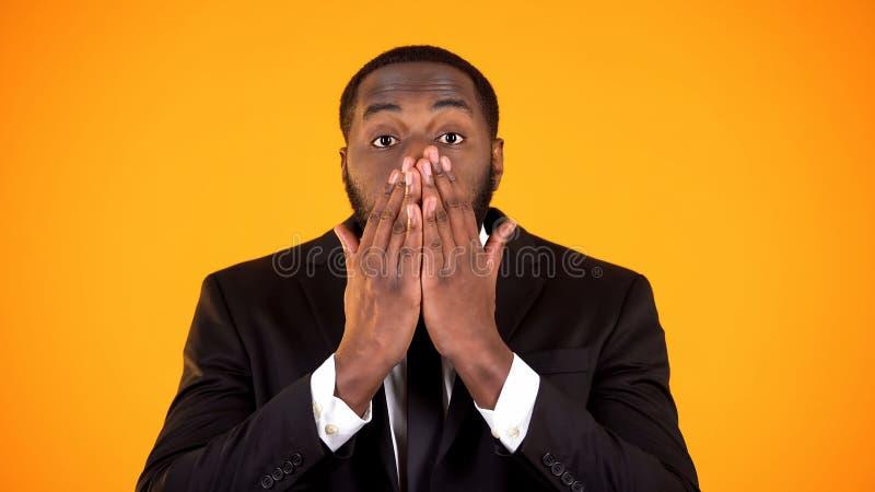 Homem afro-americano surpreendido na cara de fechamento com m?os, promo??o do businesswear foto de stock royalty free