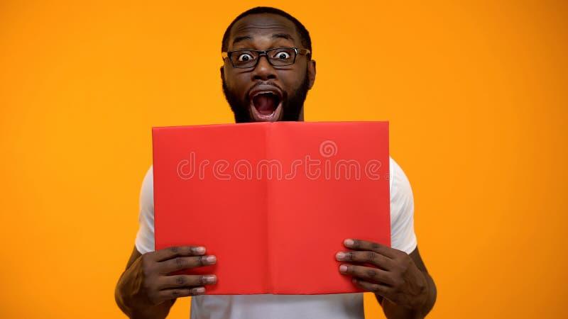 Homem afro-americano surpreendido que olha para fora o livro, informa??o interessante, estudando fotos de stock royalty free