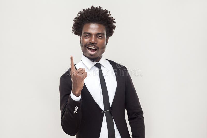 Homem afro da felicidade que olha a câmera com dedo da ideia foto de stock royalty free