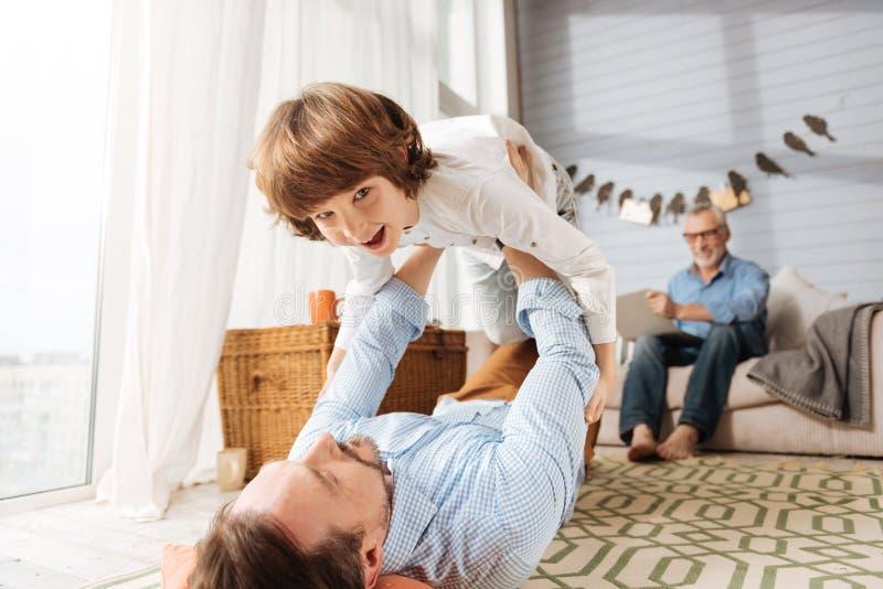 Homem agradável deleitado do pai que guarda seu filho fotografia de stock