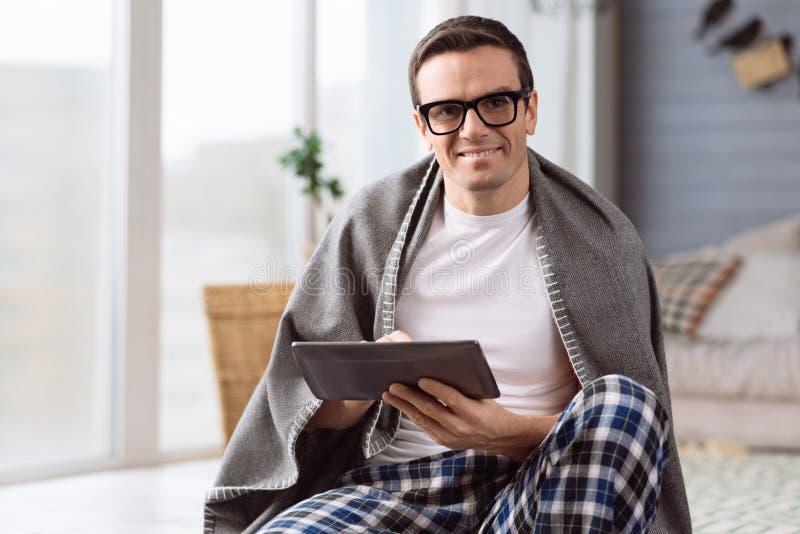 Homem agradável deleitado que guarda uma tabuleta imagens de stock royalty free