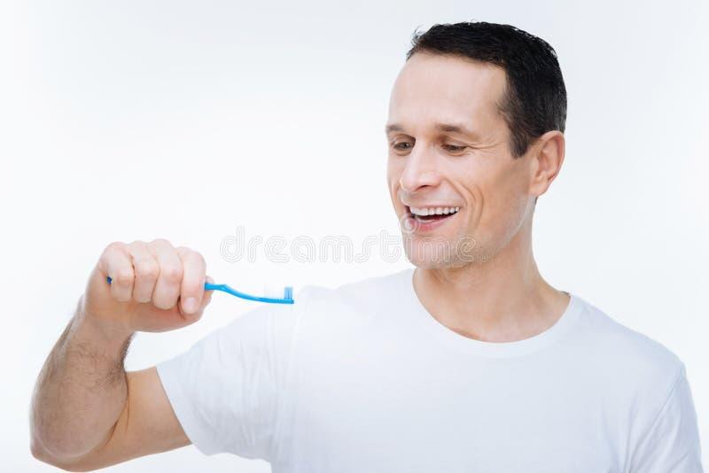 Homem agradável deleitado que olha sua escova de dentes imagem de stock
