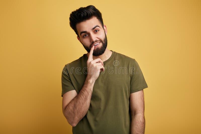 Homem agradável impressionante com um dedo em sua boca que olha a câmera fotografia de stock royalty free