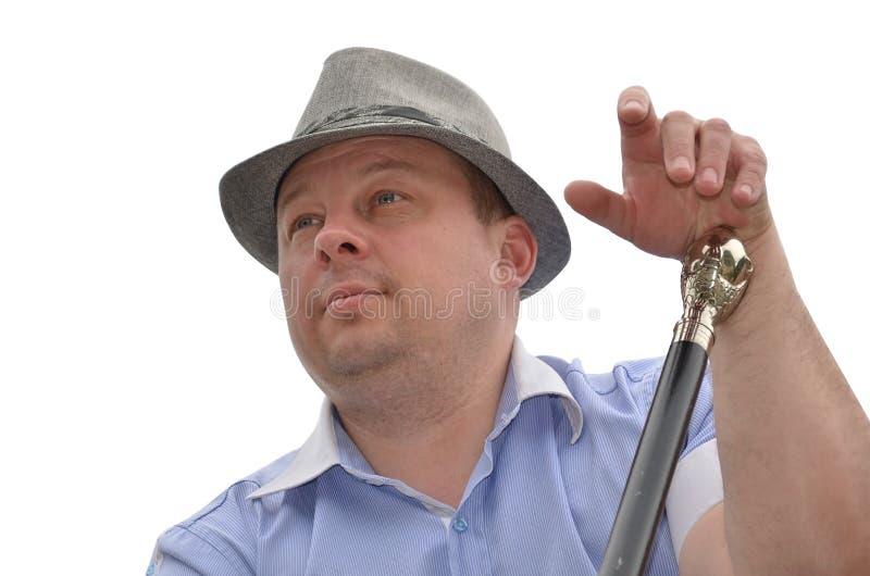 homem agradável no chapéu com o bastão no fundo branco imagens de stock royalty free