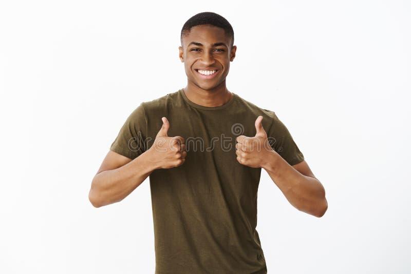Homem alegre afro-americano masculino considerável amigável que mostra os polegares acima do gesto e que sorri amplamente, gostan imagem de stock royalty free