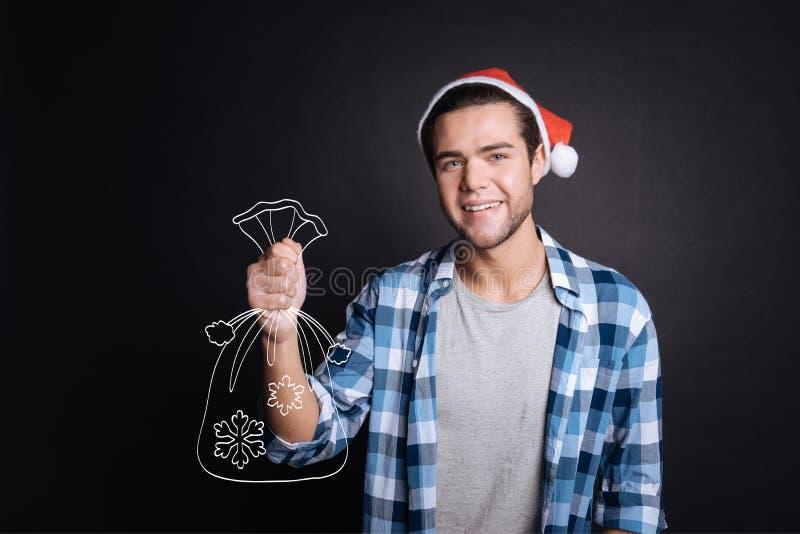 Homem alegre atrativo que guarda presentes de Natal foto de stock royalty free