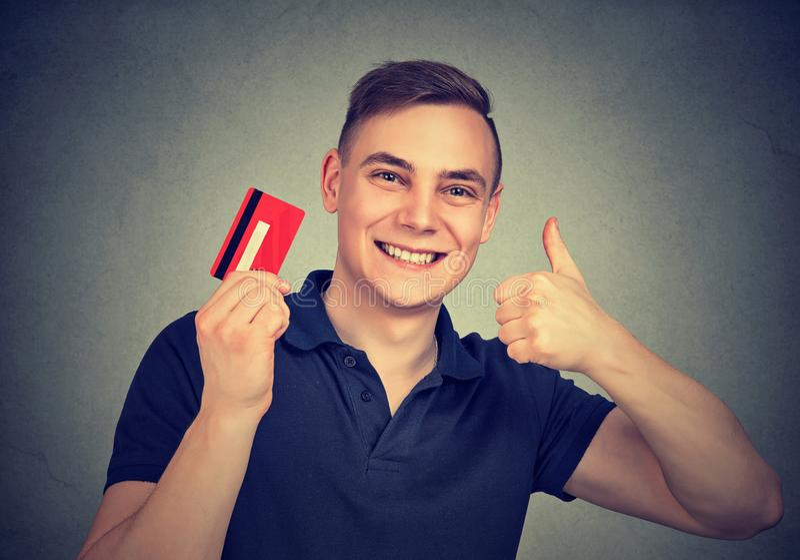 Homem alegre com o cartão de crédito que mostra o polegar acima fotografia de stock royalty free