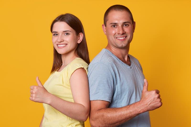 Homem alegre de Manetic que está de volta de volta à mulher moreno nova, levantando as mãos, fazendo o gesto, mostrando sua satis imagem de stock