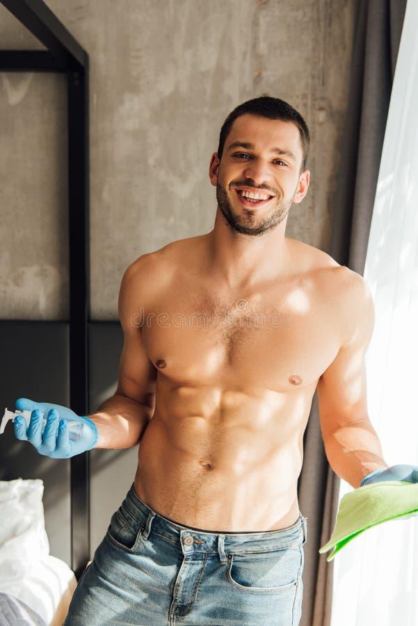 Homem alegre e muscular em luvas de borracha segurando pano e garrafa com líquido antibacteriano em casa fotos de stock
