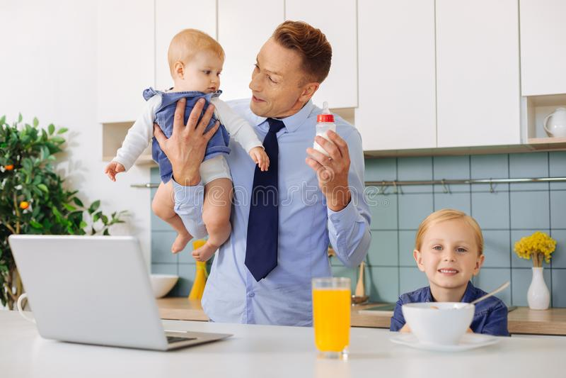 Homem alegre feliz que come o café da manhã com suas filhas fotos de stock royalty free