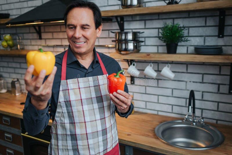 Homem alegre no suporte do avental sozinho na cozinha Guarda dois pimentas e olhares em um deles Guy Smile foto de stock royalty free