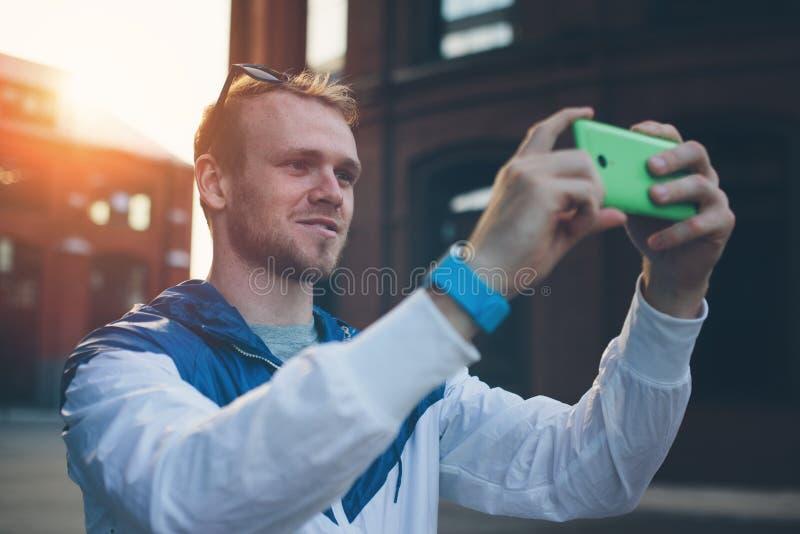 Homem alegre novo que toma a foto com o smartphone na rua foto de stock