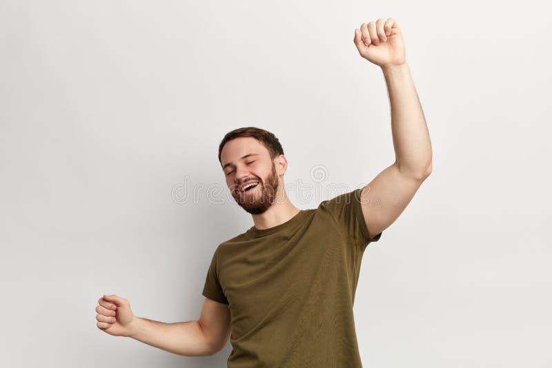 Homem alegre positivo no t-shirt verde que tem o divertimento no estúdio imagens de stock royalty free