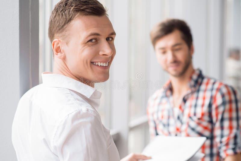 Homem alegre que está com seu colega fotografia de stock
