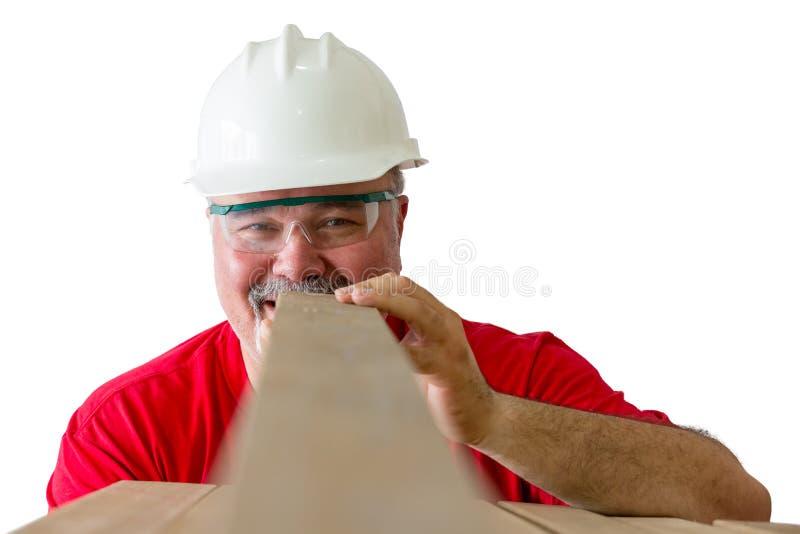 Homem alegre que inspeciona a qualidade da prancha de madeira imagens de stock