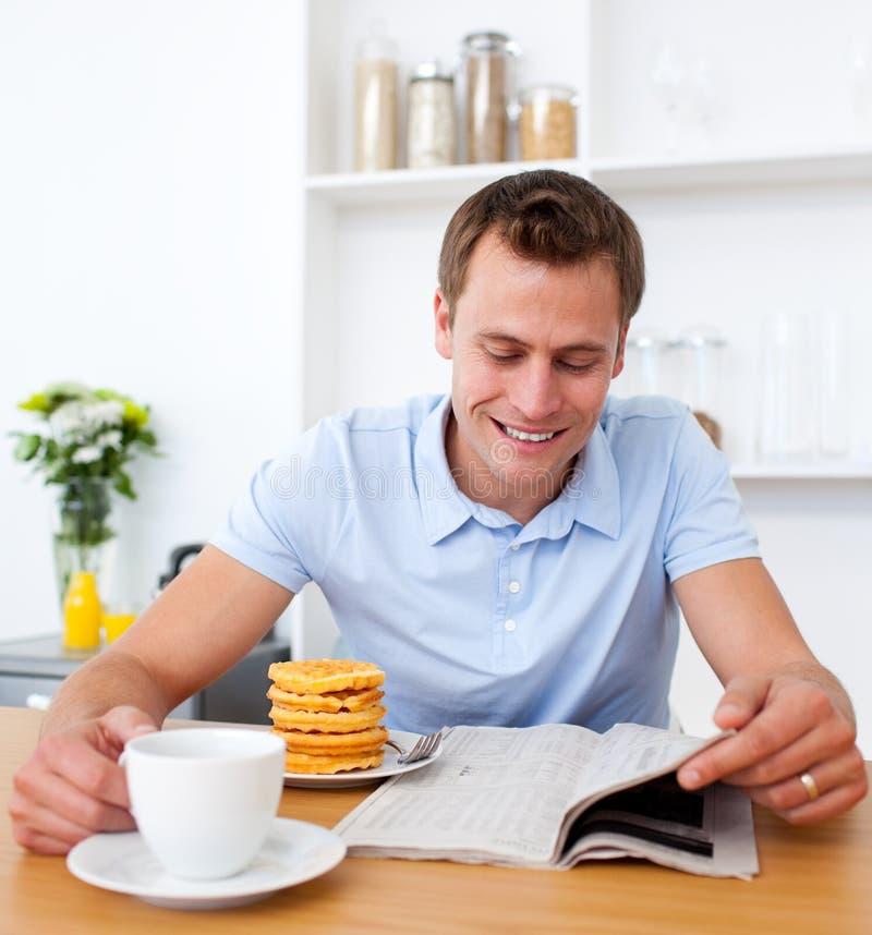 Homem alegre que lê um jornal durante o pequeno almoço fotografia de stock royalty free