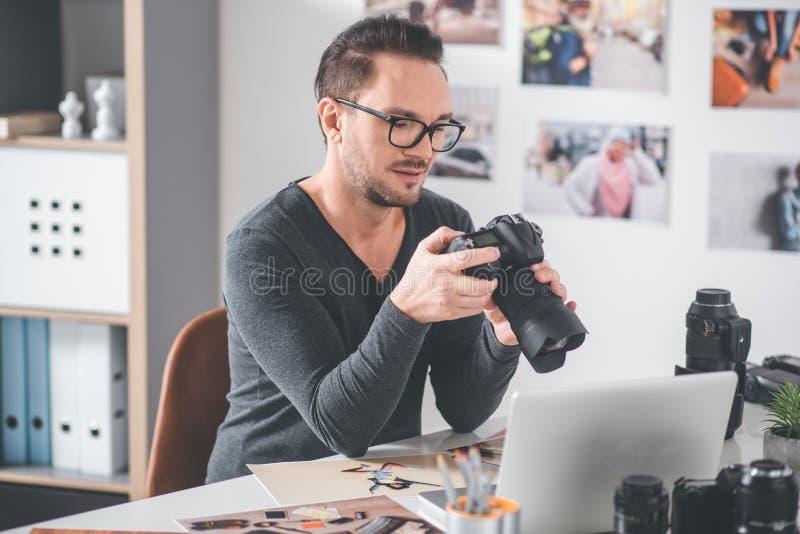 Homem alegre que mantém a câmera profissional nas mãos fotografia de stock