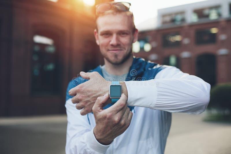 Homem alegre que mostra seus relógios espertos no pulso no por do sol fotos de stock royalty free