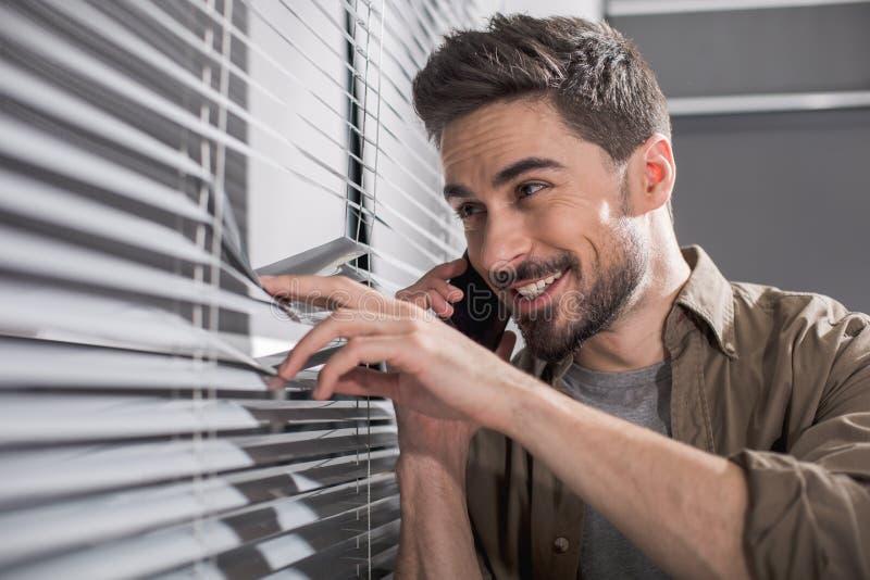 Homem alegre que olha através da janela do escritório fotos de stock