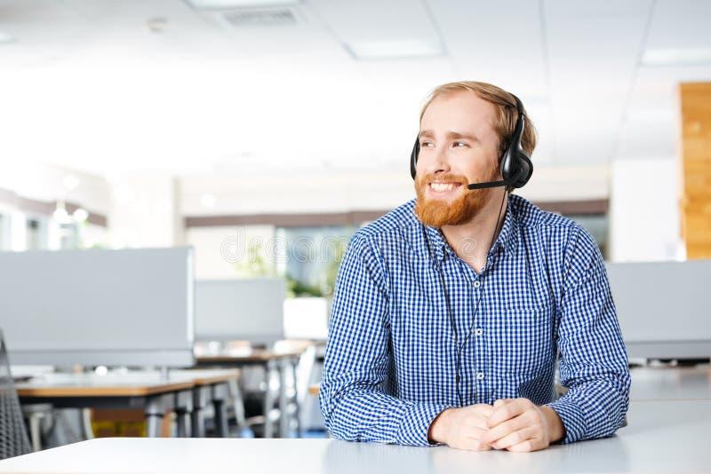 Homem alegre que senta e que usa auriculares no escritório foto de stock royalty free