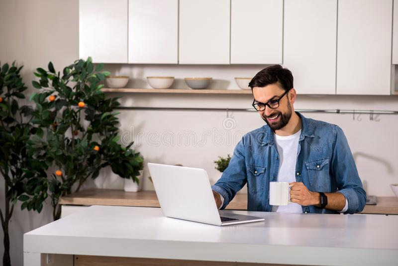 Homem alegre que senta-se na cozinha fotografia de stock royalty free