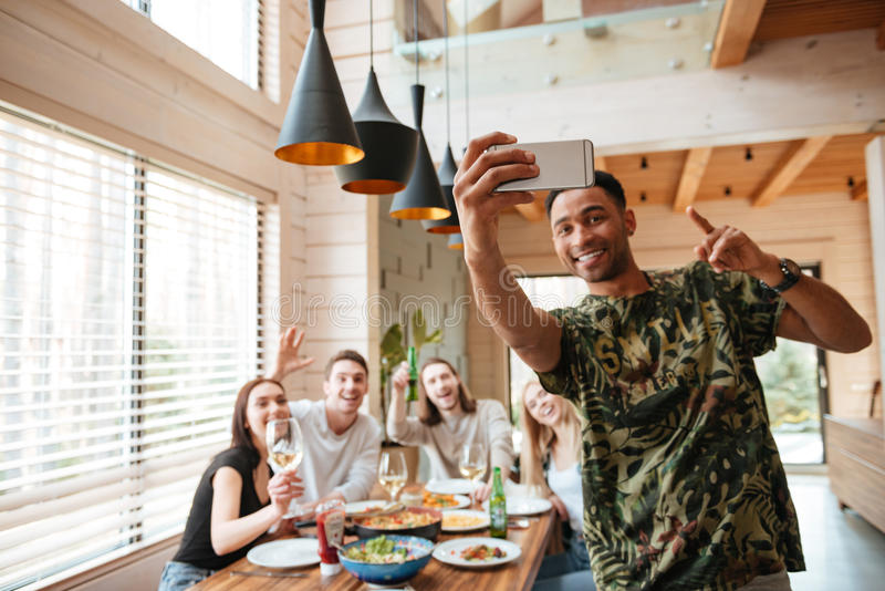 Homem alegre que toma o selfie com seus amigos na tabela fotos de stock royalty free