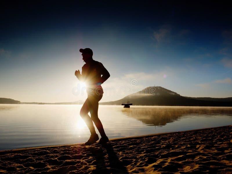 Homem alto do ajuste que corre ao longo da costa de mar na manhã Movimentar-se masculino saudável na praia foto de stock