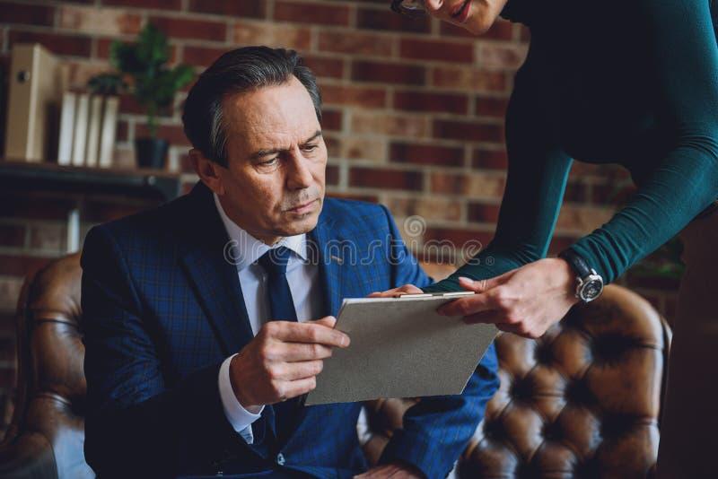Homem amadurecido sério que olha a tabuleta fotografia de stock