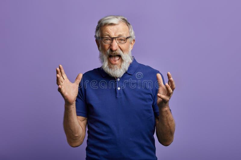 Homem amedrontado assustado com os braços aumentados que olham a câmera e que gritam imagem de stock