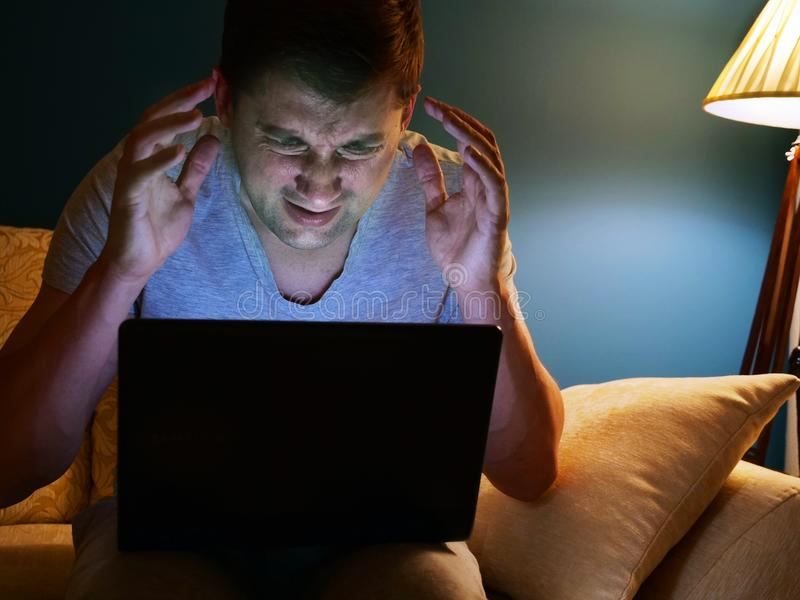 Homem amedrontado ou irritado com portátil em um sofá Tempo da noite imagens de stock royalty free