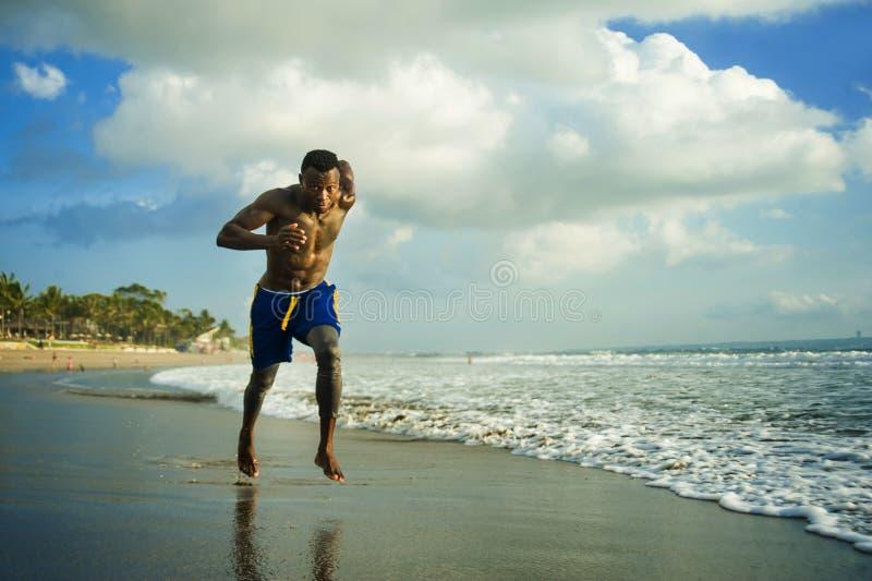 Homem americano do africano negro atlético e forte do ajuste atrativo novo que corre na praia que treina duramente e que corre na imagens de stock